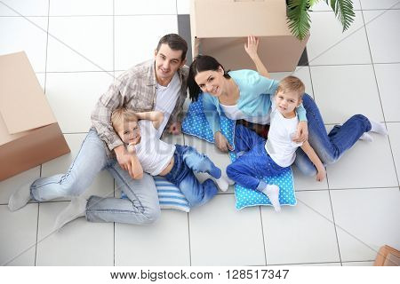Moving concept. Happy family lying on floor among cardboard boxes, top view