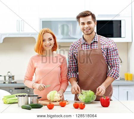 Happy couple cooking salad on the kitchen