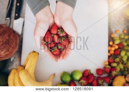 Woman Holding A Handful Of Fresh Strawberries