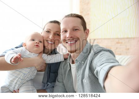 Happy couple taking a selfie with baby , close up