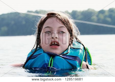 Frightened little girl in a lake wearing a life jacket.