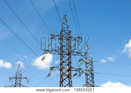 Electric pylons against the backdrop of the blue sky on a summer day