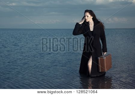 Woman in black coat standing in the sea with luggage