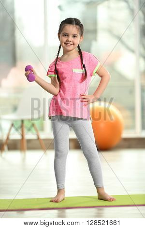 Little cute girl doing exercises with dumbbells on a mat indoor