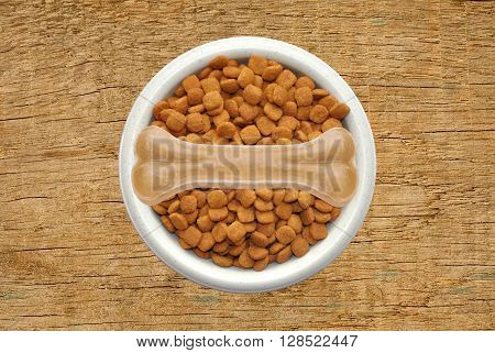 Dry dog food and bone in plate over wooden texture