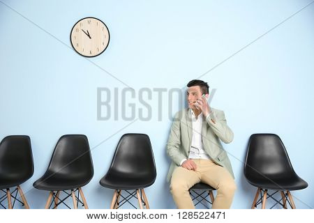 Young man in suit talking on phone and waiting for job interview