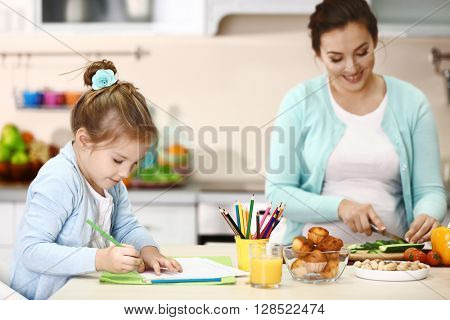 Happy pregnant woman and her child making dinner in kitchen