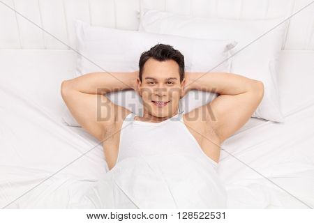 Top view shot of a joyful young man laying on a comfortable bed and looking at the camera
