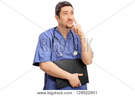 Pensive young doctor holding a clipboard and thinking isolated on white background