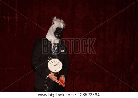 An unidentifiable man wears a rubber Horse Head a Clock around his neck and holds a rubber hot dog while posing in a Photo Booth.