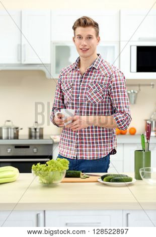 Happy handsome man with cup in bright kitchen