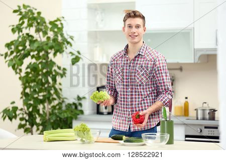 Happy handsome man with vegetables in bright kitchen