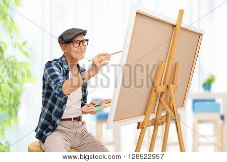 Elderly man drawing on a canvas with a paintbrush at home