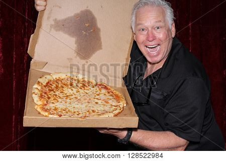 A handsome and happy man holds a Pizza Box with a pizza inside while posing for photos in a Photo Booth. Photo Booths are popular for Birthdays, Weddings, and all parties indoors or outside.