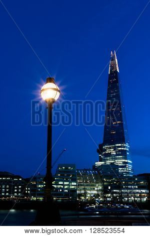 Night view of the London skyline showing The Shard and a street lamp
