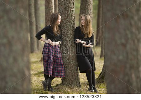 Teen girls standing in a forest near a tree talking to each other.