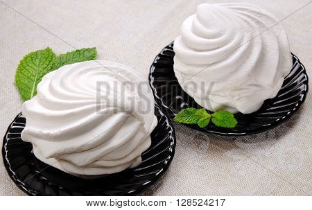 White sweet marshmallow dessert on black saucers with sprigs of fresh mint on linen fabric.