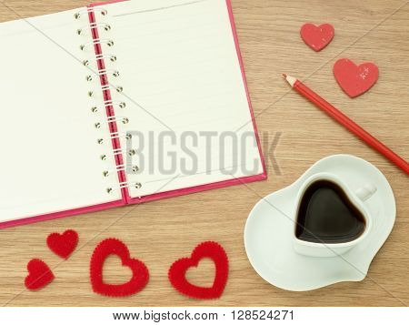 Love diary. Valentines day background with heart shape of cup with coffee red hearts book for diary and color pencils on wood floor. Love and Valentine concept.