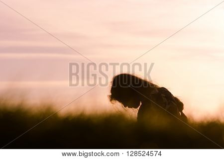 Girl silhouetted in profile in front of purple sunset. A child with long hair sitting in long grass at dusk with warm evening sky
