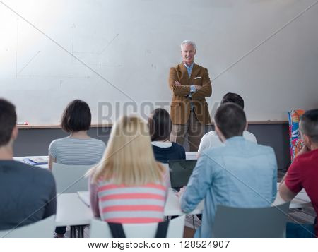 senior teacher with group of happy students in modern school classroom