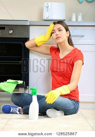 Tired beautiful woman in protective gloves after cleaning