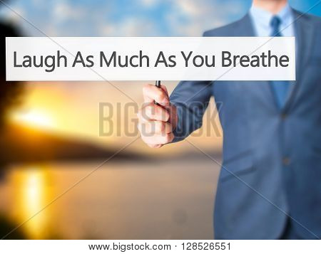 Laugh As Much As You Breathe - Businessman Hand Holding Sign