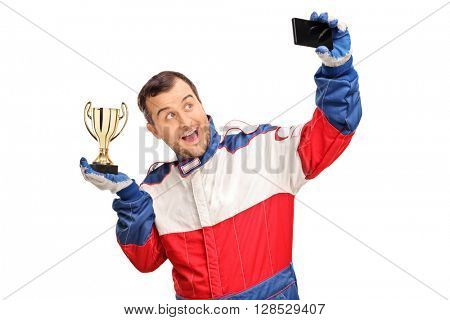 Joyful car racing champion holding a trophy and taking a selfie isolated on white background