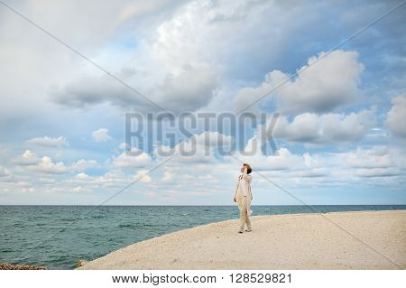 woman looking at the sea on background cloudy sky - concetual image Ostuni Apuliamediterranean Italy