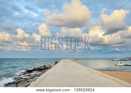 Ostuni port Apulia mediterranean sea Italy - pier sea clouds and blue sky