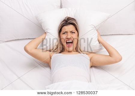Furious woman covering her ears with a pillow and trying to sleep