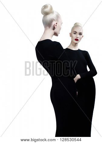 Art fashion studio portrait of elegant blonde and her reflection in the mirror