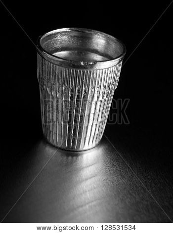 Silver thimble on a black background with a reflection