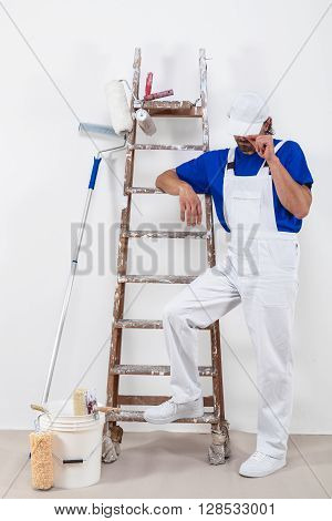 Painter In White Dungarees And Painting Tools