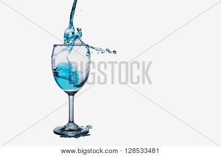 Cocktail splash into wine glass isolated on white background.