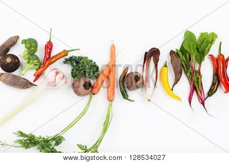 Path made from beet leaves carrots beetroot curly kale chicory chilli pepper broccoli and garlic on white background