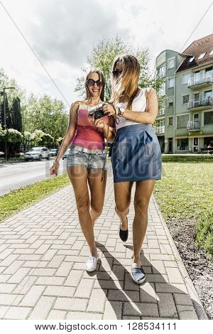 Two happy women walking with retro camera in the street at summer.