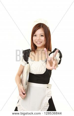 young Japanese woman wearing french maid costume showing a victory sign