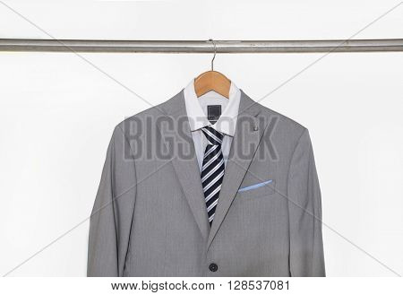 A shot of business man gray suit clothes hanging
