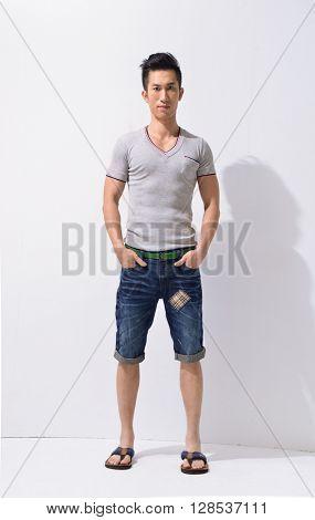 Full body Portrait of young men in jeans standing in studio