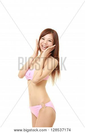 portrait of young Japanese woman in a pink bikini pleased on white background