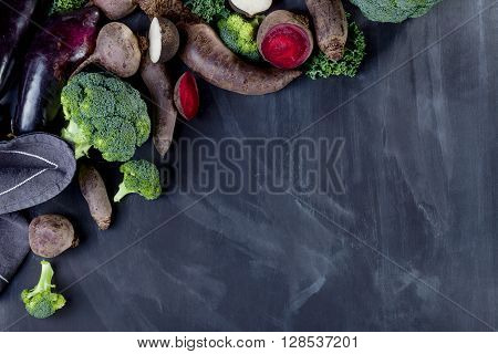 Beetroots curly kale broccoli and black turnip with cloth lying on blackboard from left top