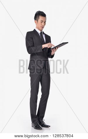 Full body Portrait of young businessman Using Digital Tablet Isolated