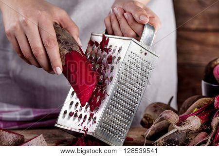 Cook in gray apron is grating a beetroot with vegetable rasper in close up