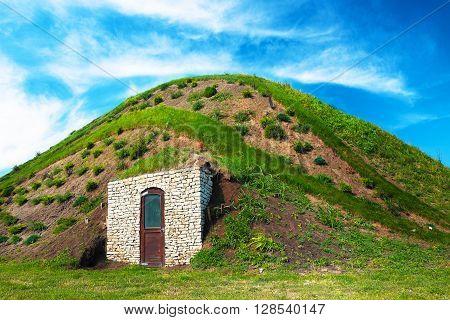 Fairy hobbit hill wih door under the blue sky