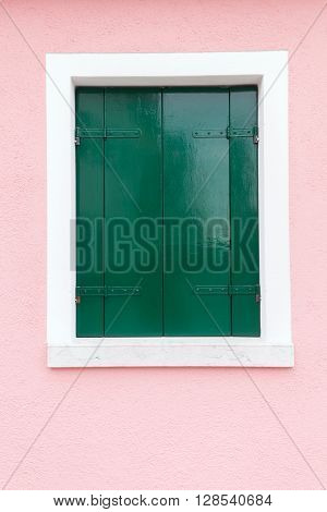 Picturesque old window with dark green shutters on light pink wall (Burano island Venice Italy)
