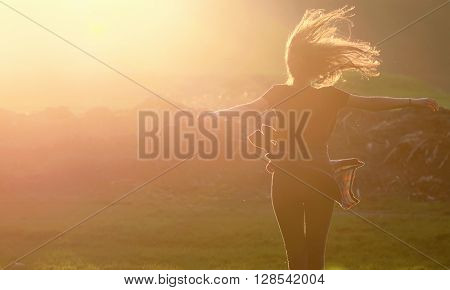 Girl  jumping up in a beautiful sunset setting