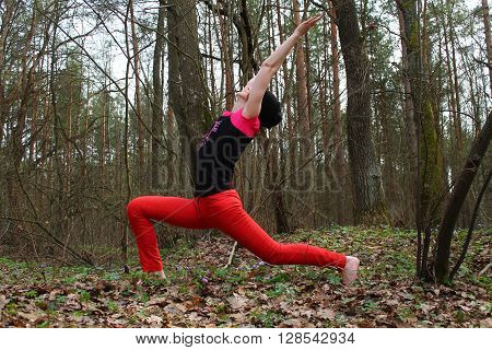 beautiful strong young woman made yoga pose(Virabxadrasana) in morning spring forest