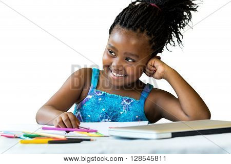 Close up portrait of little african girl at desk with color pencils and laptop.Isolated on white background.