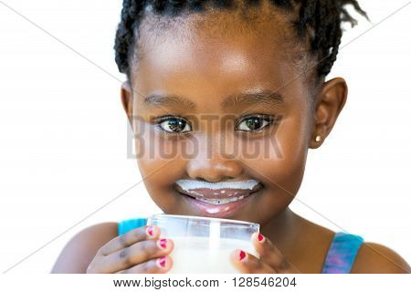 Close up face shot of sweet african girl with milk mustache.Girl holding glass of milk isolated on white background.