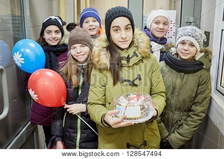 Six children stands together inside building holding air ballons and cake.